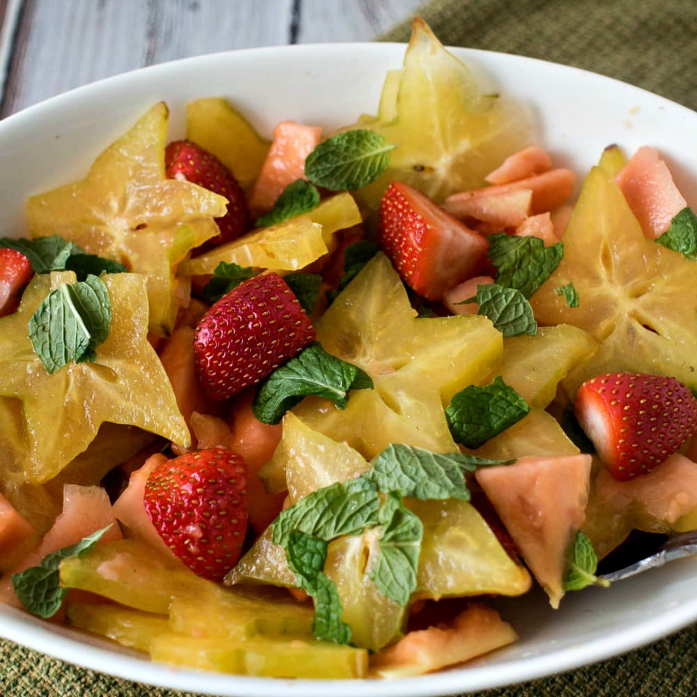 Tropical Fruit Salad - Starfruit, papaya and strawberries drizzled with lime and mint leaves #fruitsalad