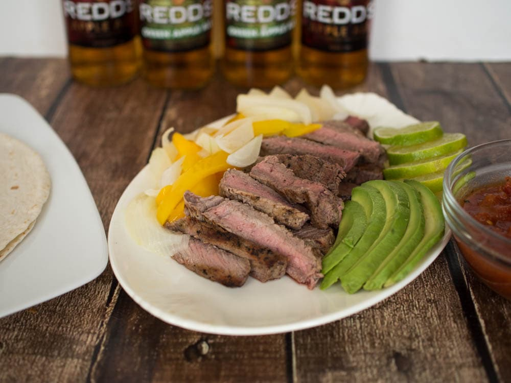 Easy Steak Fajitas with Redd's Apple Ale - steak marinaded in Redd's Apple Ale, served with onions, peppers, avocado and lime