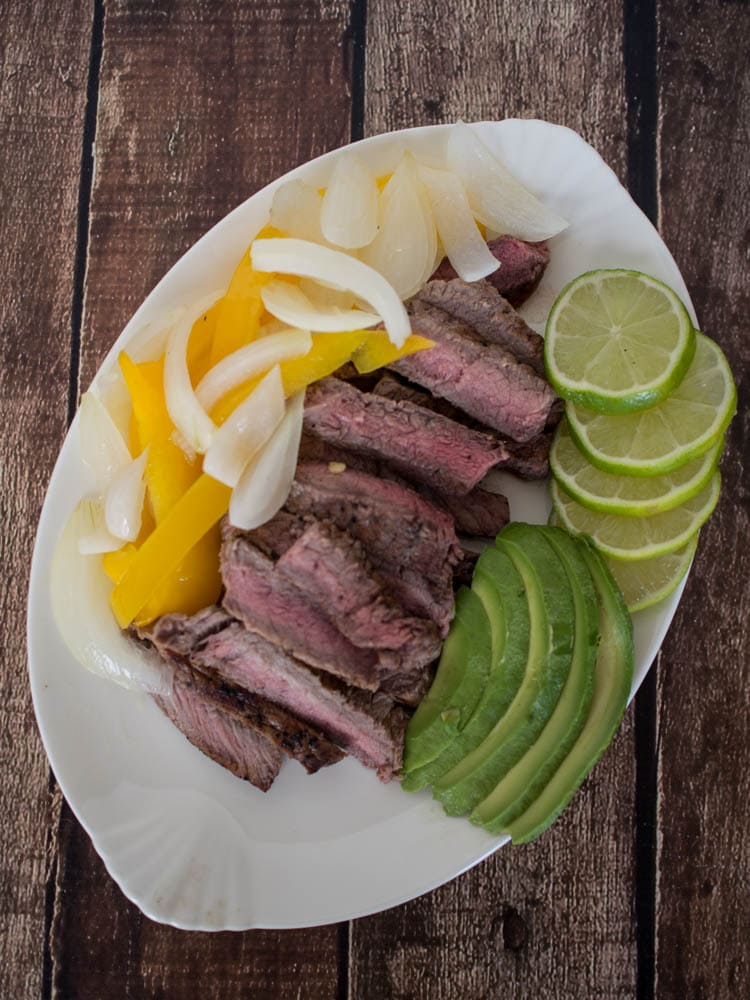 Easy Steak Fajitas Recipe - steak marinaded in Redd's Apple Ale, served with onions, peppers, avocado and lime