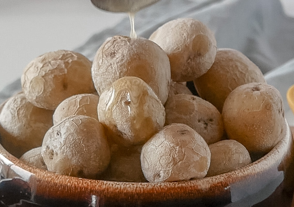 Big bowl of salt potatoes drizzled with butter