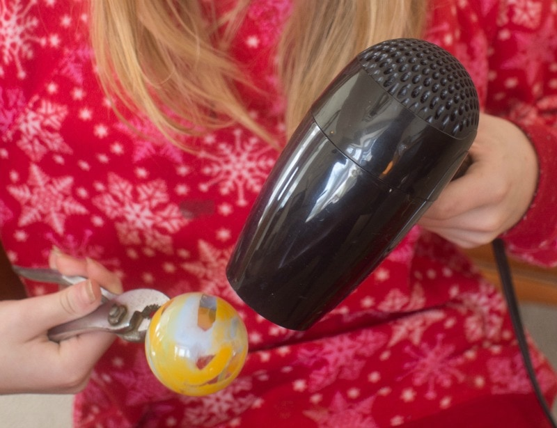 Demonstrating how to make melted crayon glass ornaments