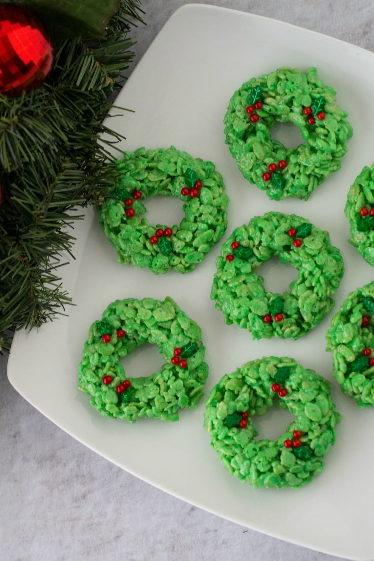 Make these cute Rice Krispie Treat Wreaths this holiday season for a simple Christmas treats! With the basic Rice Krispie treat recipe, some food coloring and decorations you can have an adorable wreath Christmas cookie. #ricekrispietreats #wreath #christmascookie #holidaybaking