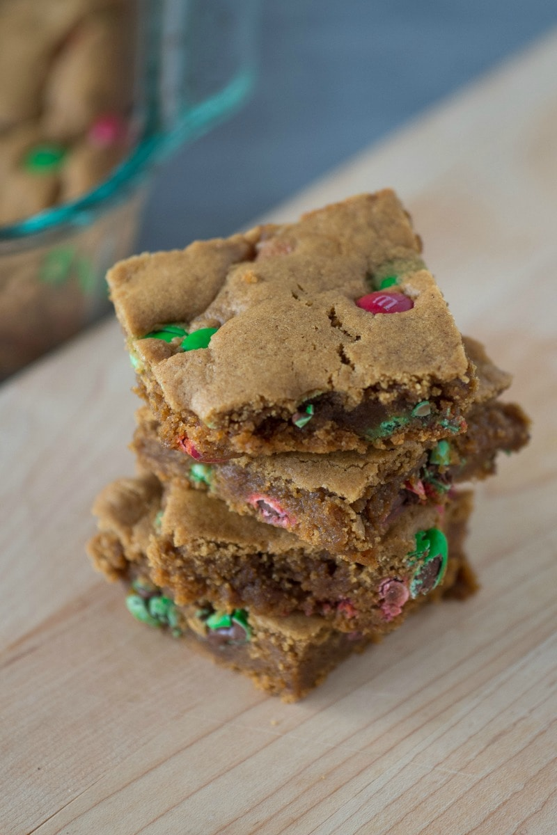 These chewy Holiday Gingerbread Cookie Bars combine rich molasses with ginger and cinnamon for a spice filled bar with added M&Ms! A quick and easy alternative to making gingerbread men for your holiday dessert table. #gingerbread #christmascookies #holidaybaking #christmas