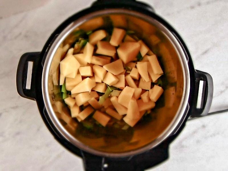Adding potatoes to the pressure cooker potato soup