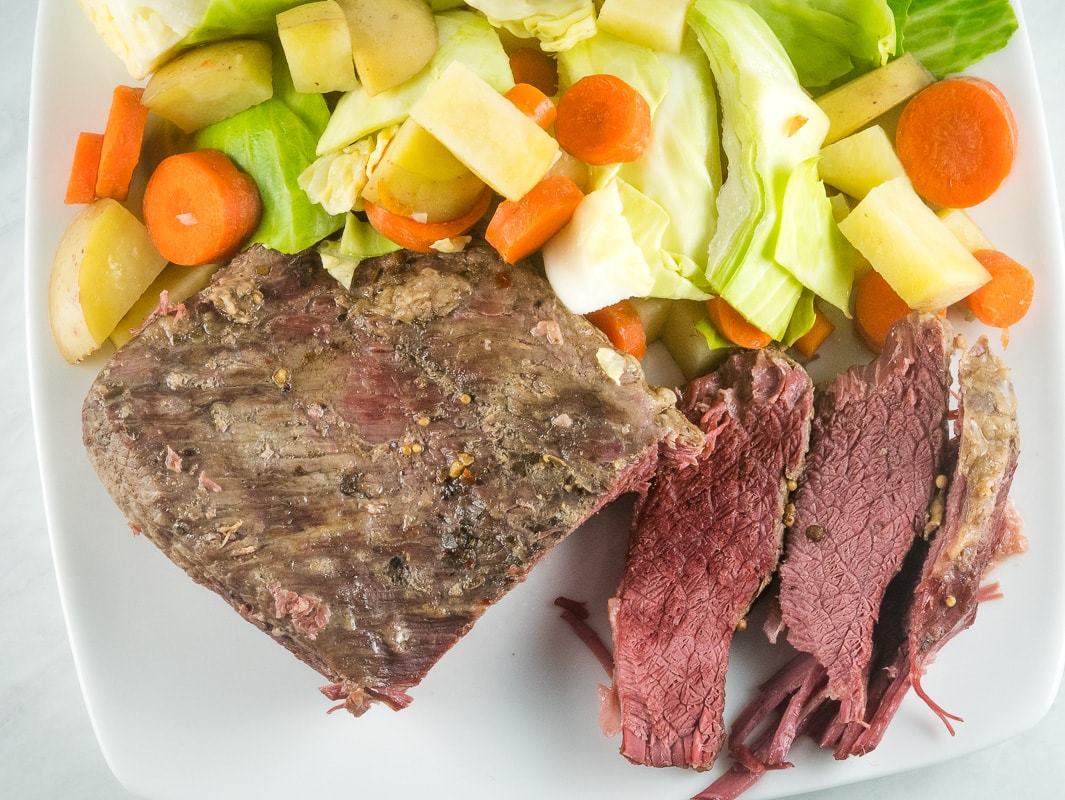 Overhead view of pressure cooker corned beef with cabbage, carrots and potatoes