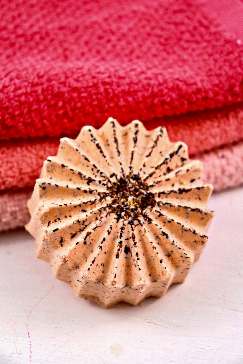 Tea infused bath bomb made with blood orange tea near a stack of towels