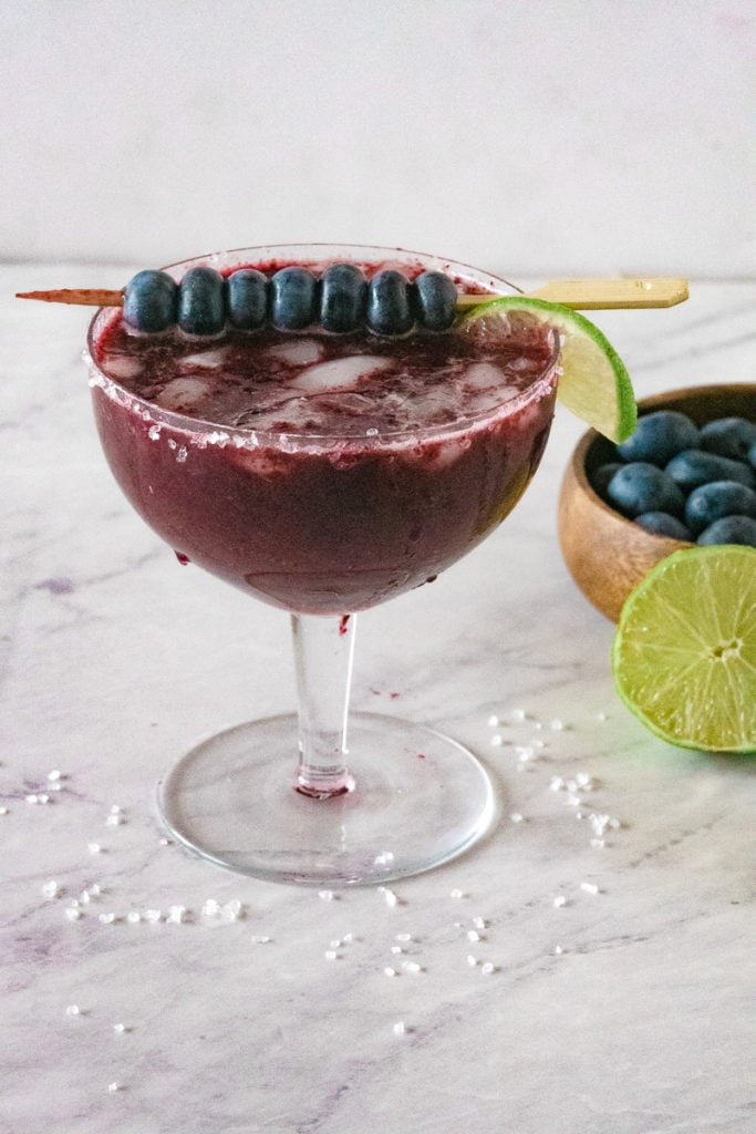 blueberry margarita in a glass garnished with lime and blueberries