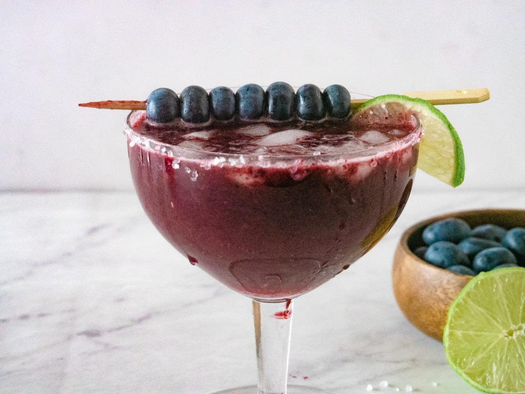close up view of blueberry margarita in a glass