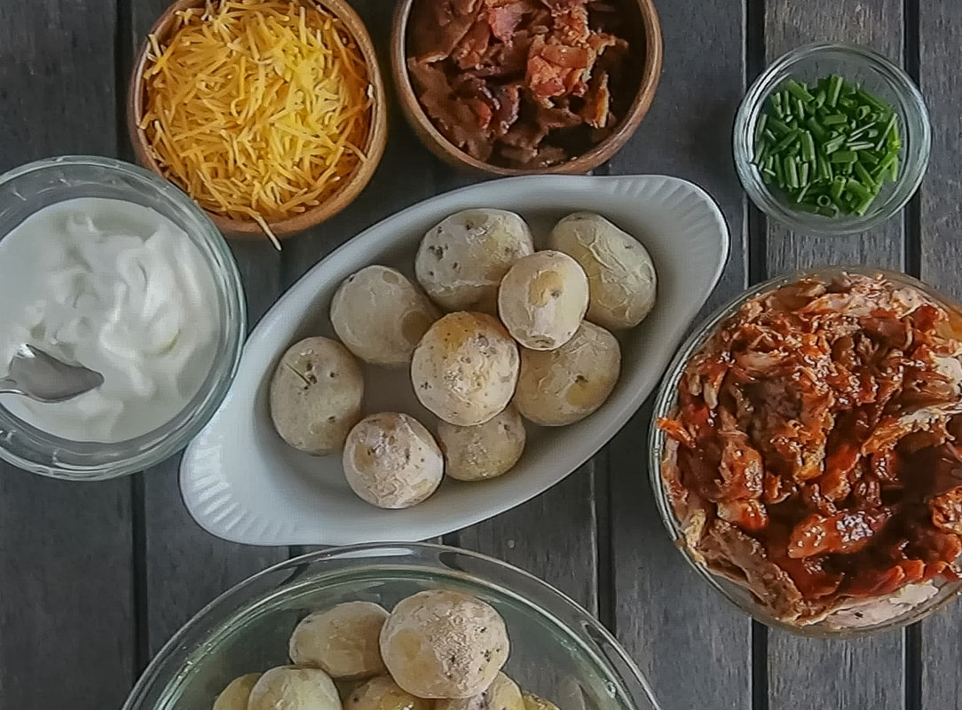 Salt potatoes in bowl surrounded by loaded salt potato toppings