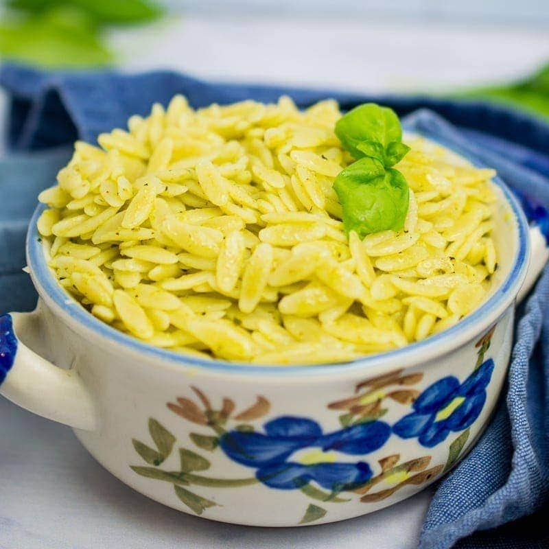 bowl full of orzo pasta salad with basil on top