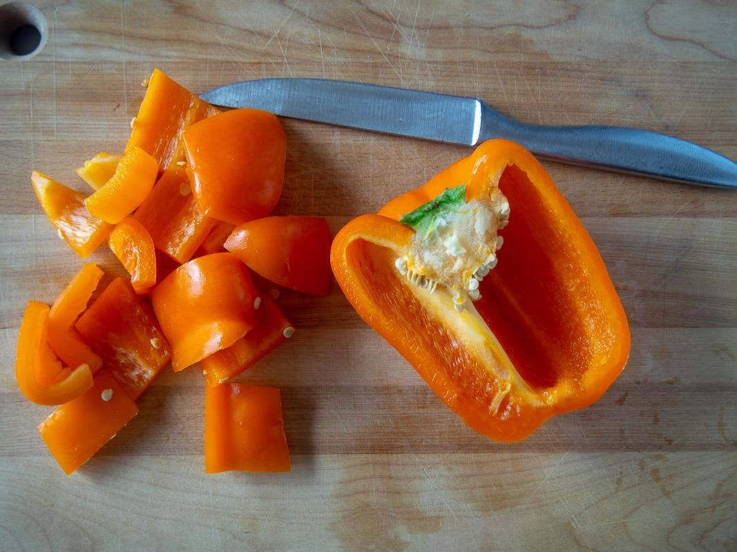 Slicing orange pepper for pork kabobs