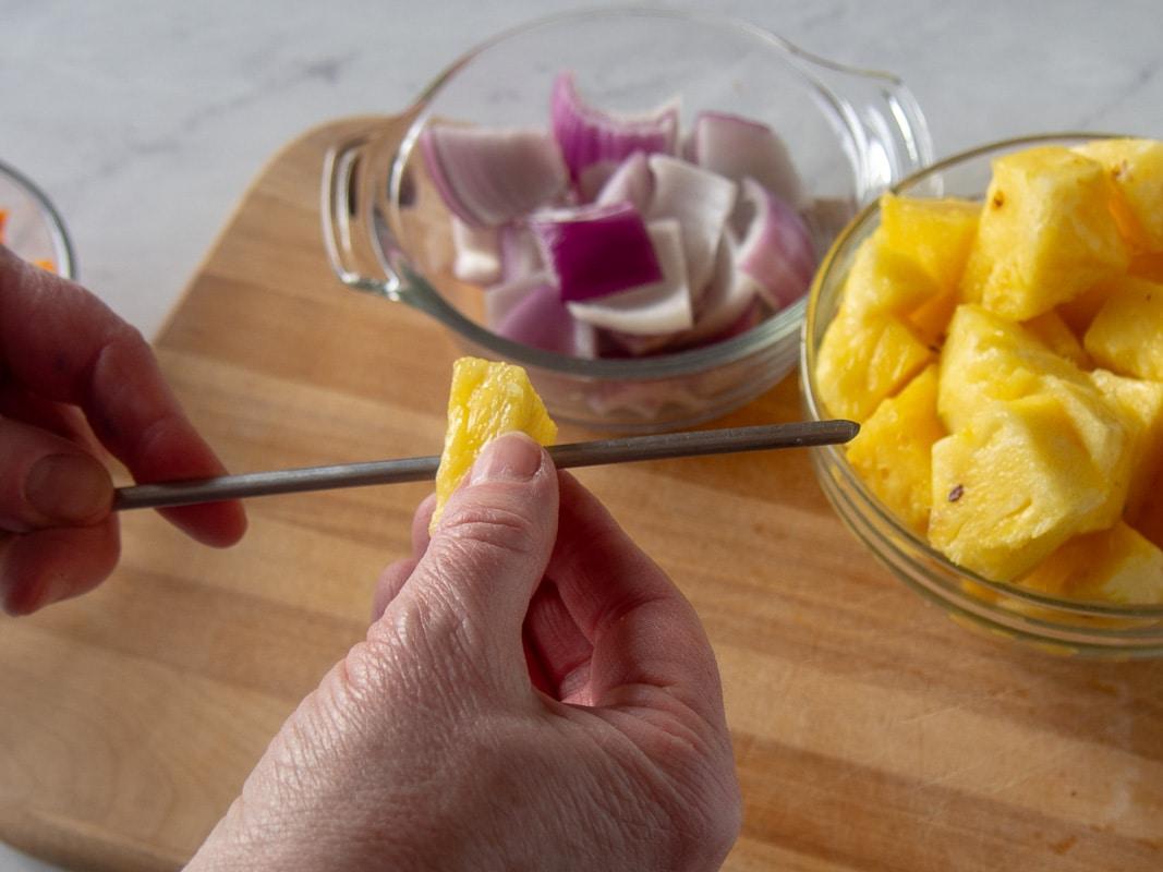 Threading pineapple on skewer for making pork kabobs
