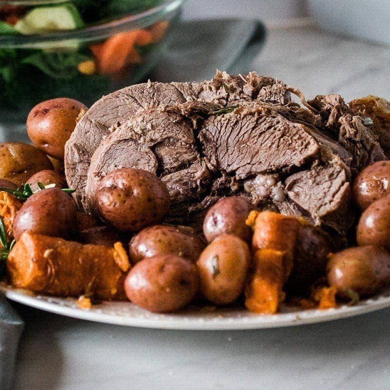 sliced instant pot leg of lamb on a plate with potatoes and carrots
