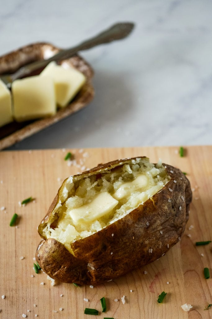 air fryer baked potato on a wooden cutting board