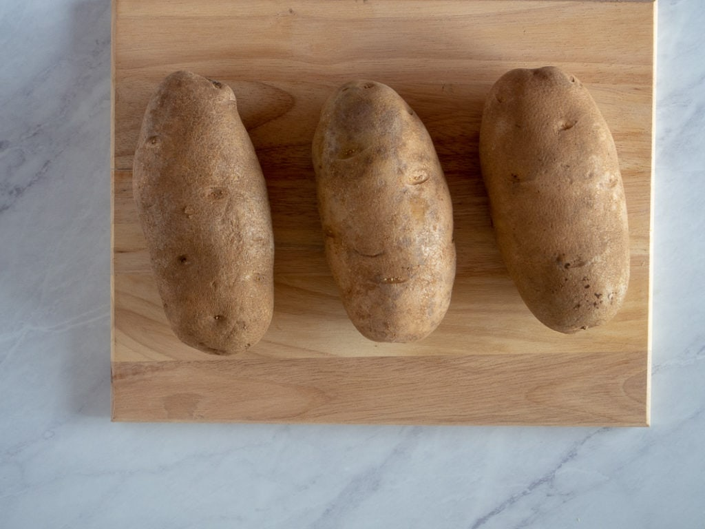Potatoes on a cutting board ready for baking