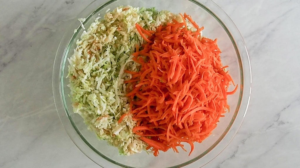 shredded cabbage and carrots in a bowl for making coleslaw