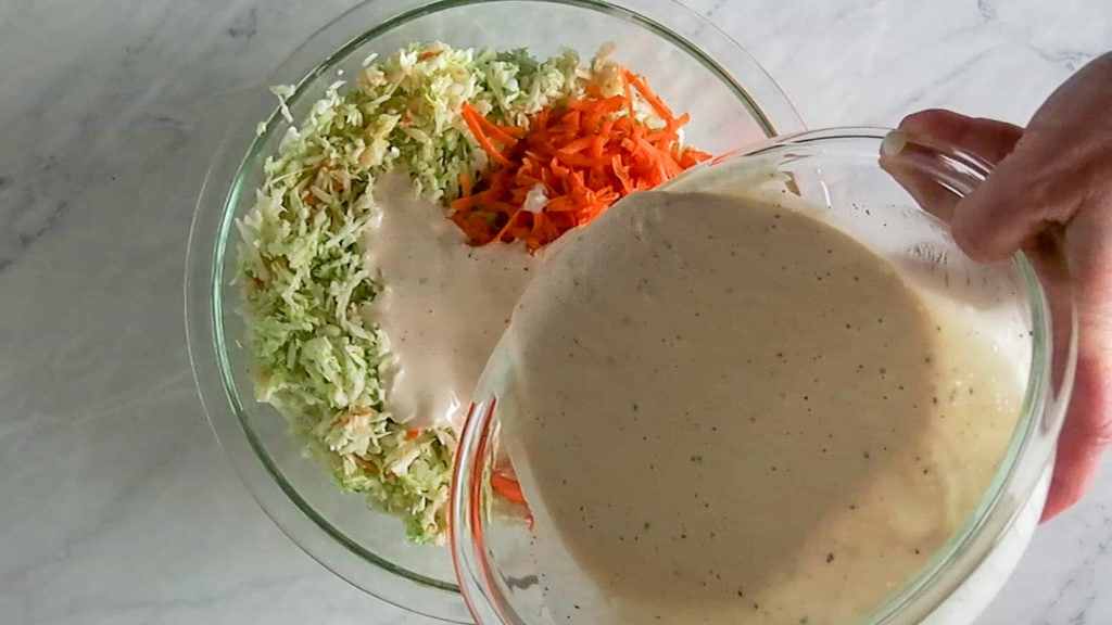 Pouring the dressing onto the blue cheese coleslaw