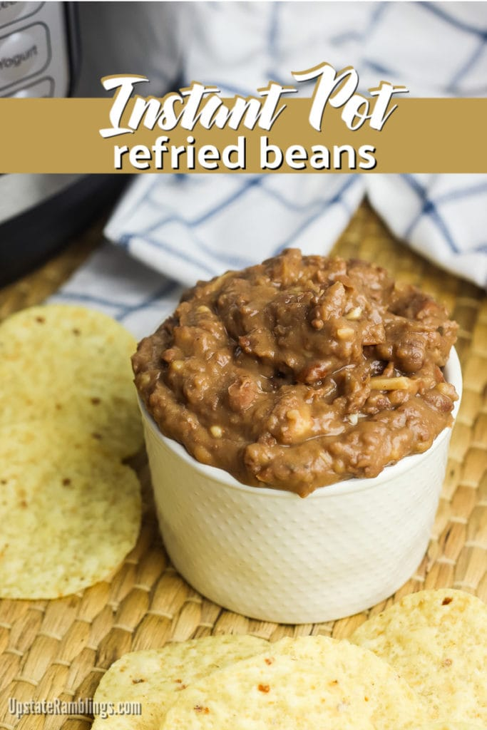 Instant Pot refried beans in a white bowl with tortilla chips