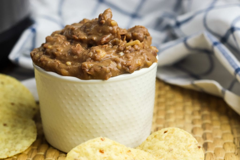 Pressure cooker refried beans in a bowl with tortilla chips