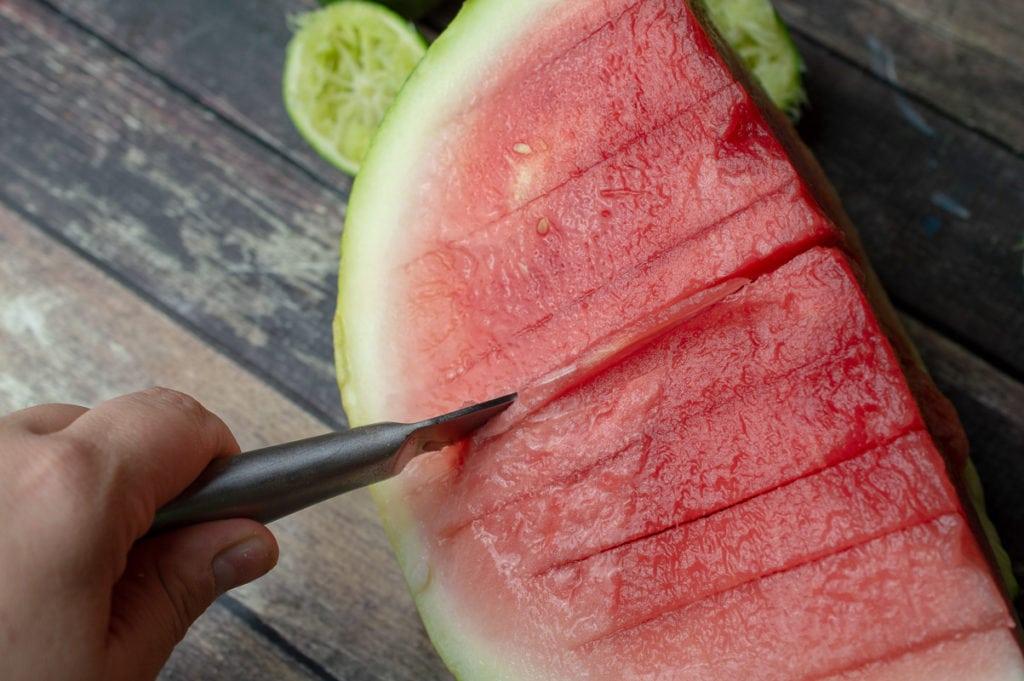 slicing watermelon to make a vodka watermelon cocktail