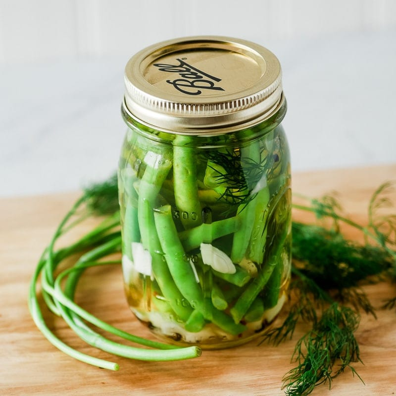 jar of dilly beans on a cutting board with dill