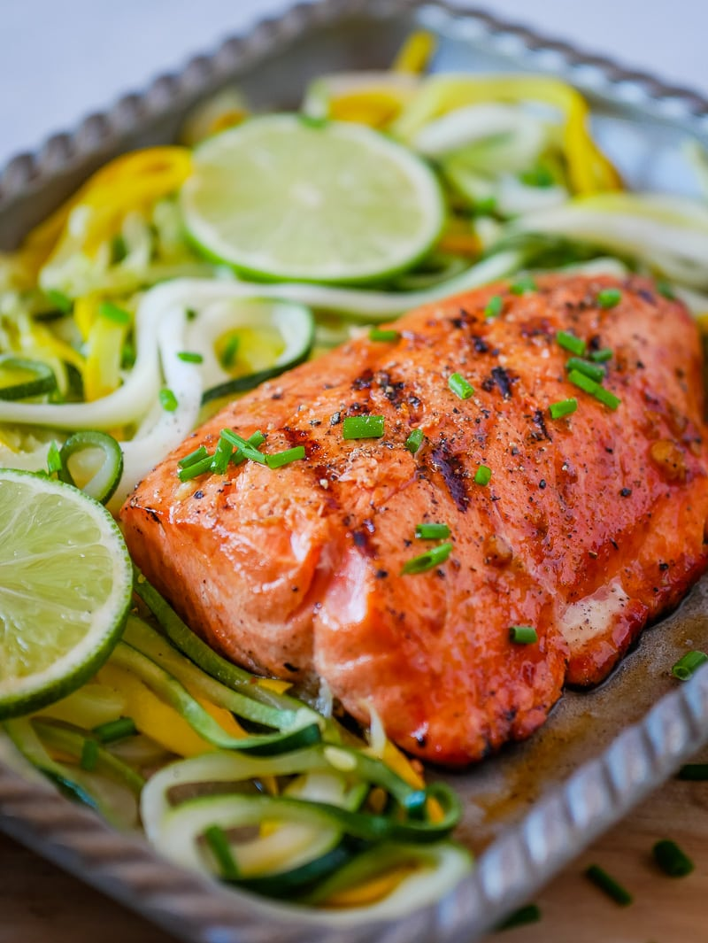 spicy grilled salmon on a platter with lime