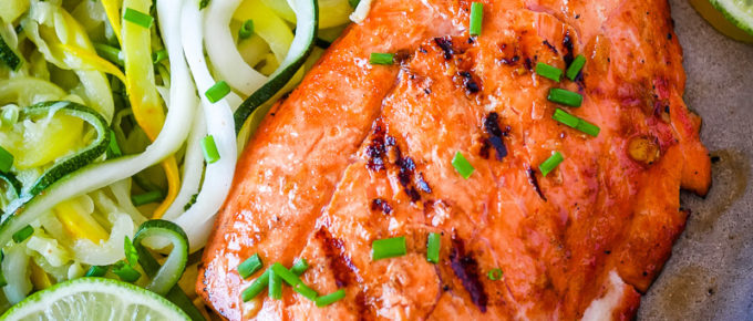 grilled salmon on a platter with lime and summer squash