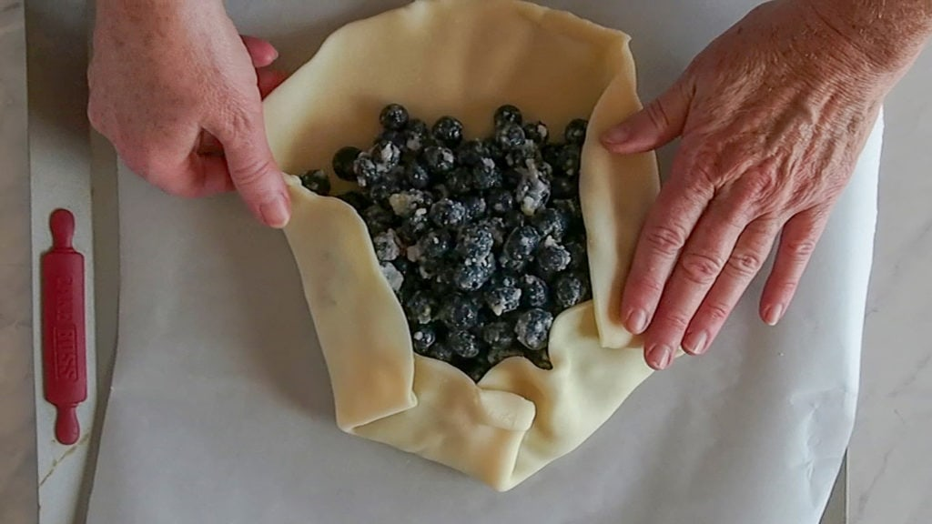 folding the pie crust for a blueberry galette