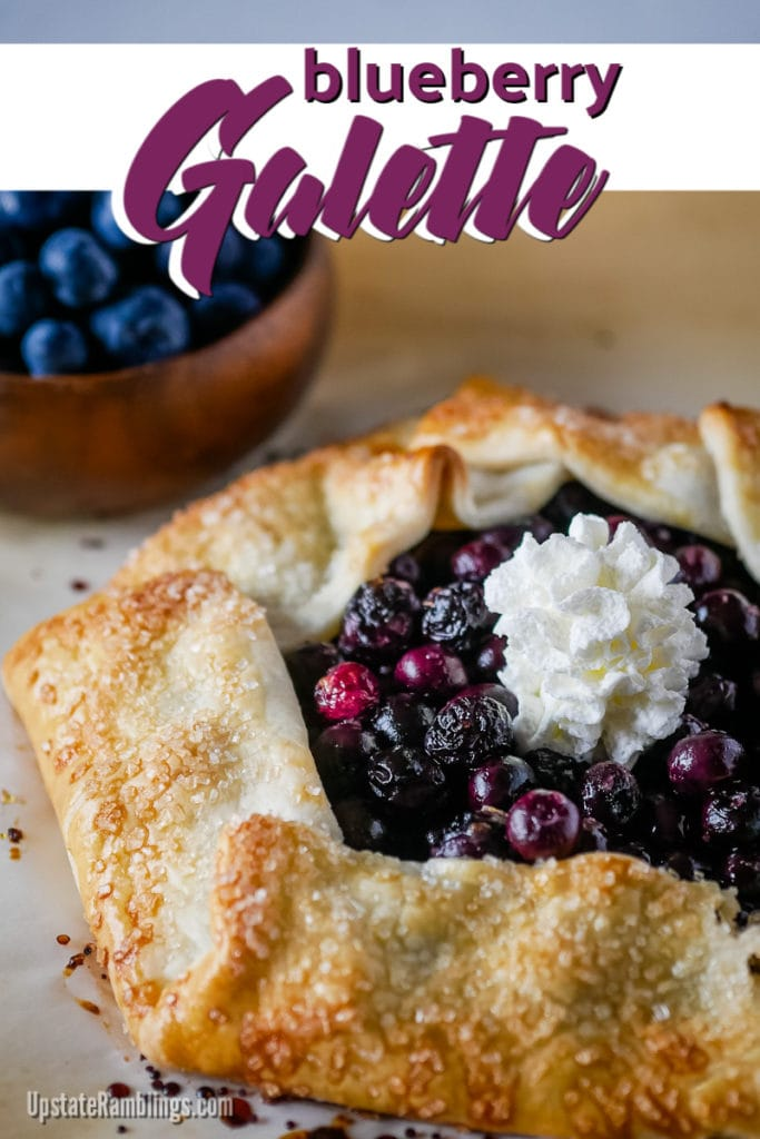 blueberry galette with whipped cream on top and a bowl of blueberries in the background