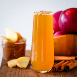 glass of apple cider cocktail on a cutting board with apples in the background